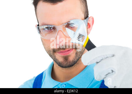 Repairman looking through adjustable wrench - Stock Photo