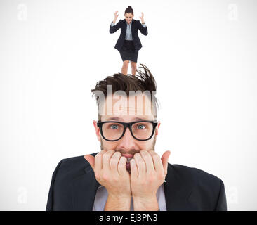 Composite image of geeky nervous businessman looking at camera - Stock Photo