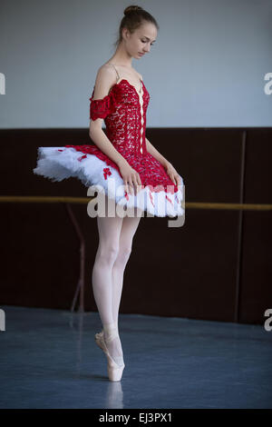 Slender ballerina standing on pointe in the ballroom looking dow - Stock Photo