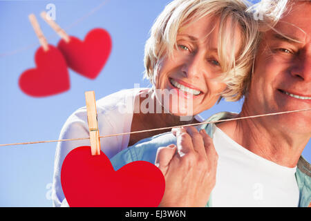 Composite image of happy senior man giving his partner a piggy back - Stock Photo