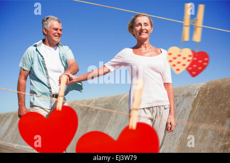 Composite image of happy senior couple walking on the pier - Stock Photo