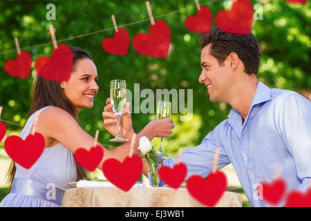 Composite image of couple with champagne flutes sitting at outdoor café - Stock Photo