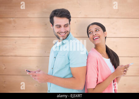 Composite image of happy couple sending text messages - Stock Photo