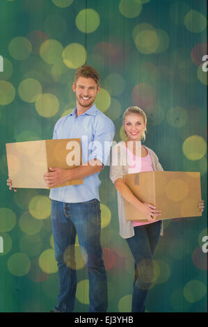 Composite image of attractive young couple carrying moving boxes - Stock Photo