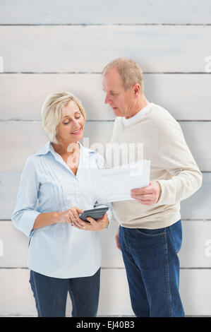 Composite image of mature couple working out their bills - Stock Photo