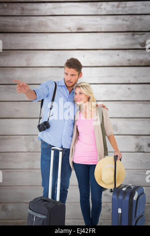 Composite image of attractive young couple ready to go on vacation - Stock Photo