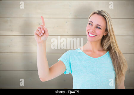 Composite image of portrait of smiling blonde pointing up - Stock Photo