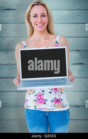 Composite image of smiling blonde presenting her laptop