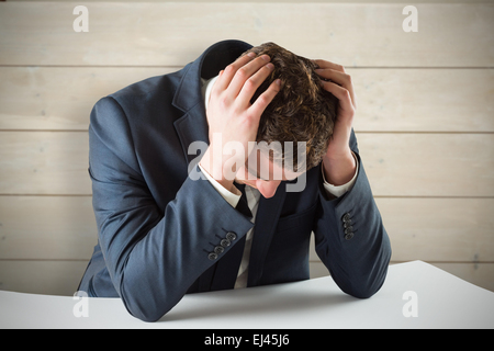 Composite image of businessman with head in hands - Stock Photo