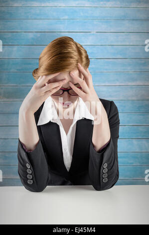 Composite image of redhead businesswoman with head in hands - Stock Photo
