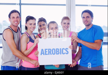 Aerobics against portrait of a group of fitness class holding blank paper - Stock Photo