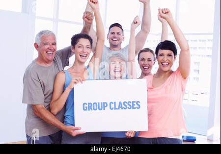 Group classes against portrait of happy fit people holding blank board - Stock Photo