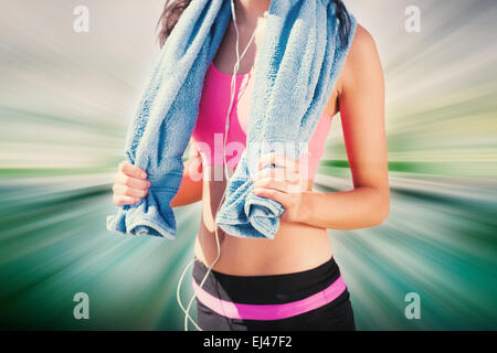 Composite image of mid section of healthy woman with towel around neck on beach - Stock Photo