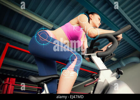 Composite image of determined young woman working out at spinning class - Stock Photo