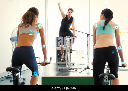 Composite image of fit women doing a spin class with enthusiatic instructor - Stock Photo
