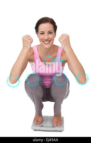 Composite image of portrait of a young woman cheering on weight scale - Stock Photo