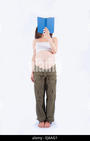 eight month pregnant woman green trousers bare belly stand reading a blue book isolated over white background - Stock Photo