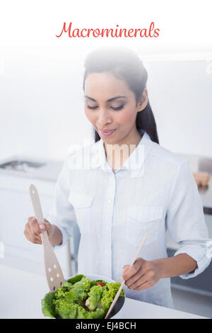 Macrominerals against lovely peaceful woman preparing salad in kitchen - Stock Photo