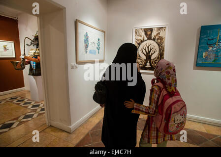 Young woman in traditional Muslim clothes discuss contemporary painting with her daughter during 2nd Grand Festival - Stock Photo