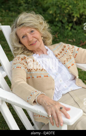 Elderly woman sitting in a chair in the garden - Stock Photo