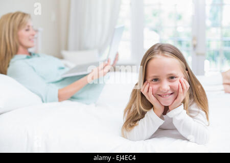 Little girl looking at camera while mother using laptop - Stock Photo