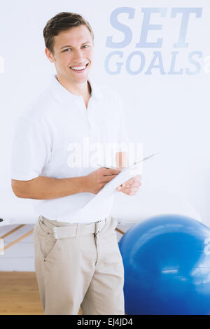Composite image of smiling male trainer with clipboard in gym at hospital - Stock Photo