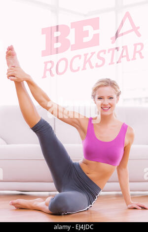 Composite image of athletic blonde sitting on floor stretching leg up smiling at camera - Stock Photo