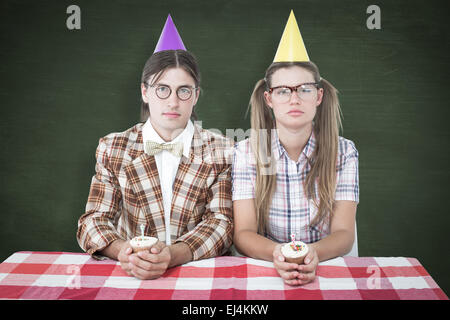 Composite image of unsmiling geeky hipsters celebrating birthday - Stock Photo