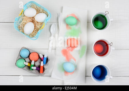 High angle still life shot of Easter Egg dying,cups full of dye, a basket of egg, dyed eggs, and markers for decoration. - Stock Photo