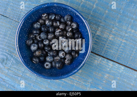 High angle image of an enamelware bowl full of fresh picked blueberries. Horizontal format on a blue wood kitchen - Stock Photo