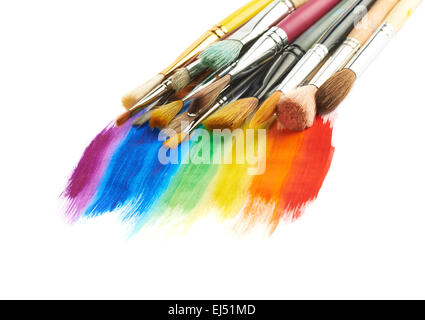Pile of different brushes over the paint strokes - Stock Photo