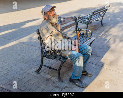 A Cuban male senior citizen with a cigar sits on a bench with a baseball type hat looking up at the sky in late - Stock Photo