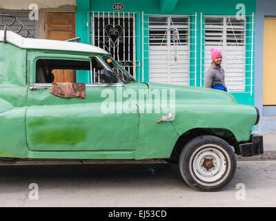 an afro cuban man wearing a hot pink wool hat stands by a green and