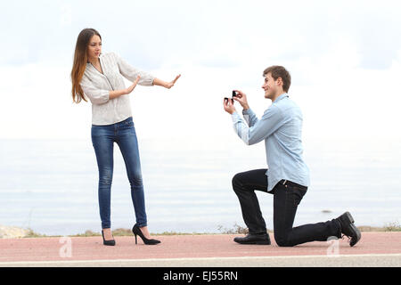 Proposal rejection when a happy man asks in marriage to a woman on the beach - Stock Photo
