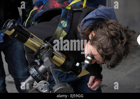 a boy is looking through an amateur telescope to observe the solar eclipse through the lens Barcelona - Stock Photo