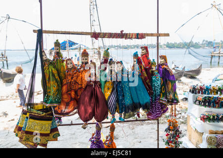 Typical traditional colourful marionette puppets on display for sale as tourist souvenirs on the beach at Fort Cochin, - Stock Photo