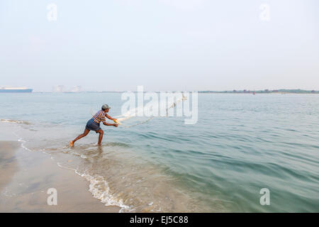 Local fisherman fishing from the shore using traditional methods, casting his net, Fort Cochin, Kerala, southern - Stock Photo