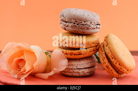 Caramel and chocolate macaroons with rose on orange and dark wood table setting. - Stock Photo