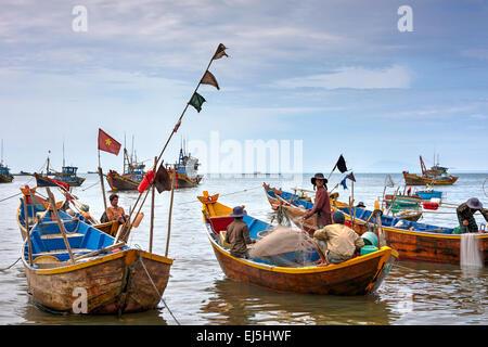 Vietnamese fishermen on traditional wooden boats at Mui Ne Fishing Harbour. Mui Ne, Binh Thuan Province, Vietnam. - Stock Photo