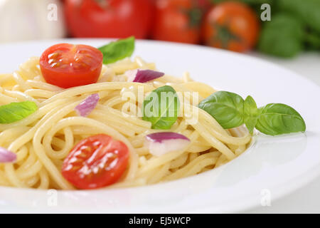 Spaghetti noodles pasta food meal with tomatoes and basil on plate - Stock Photo