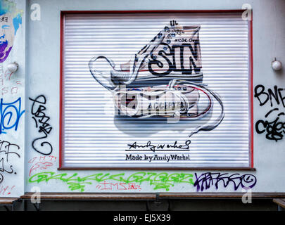 Advertisement for Converse trainers, chucks named after Chuck Taylor amongst graffiti on shop blind, Mitte Berlin - Stock Photo