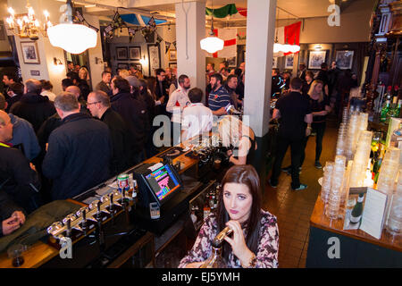 Bar and barmaid / staff / barman man & rugby fan fans at busy The Bear pub / public house. Twickenham UK; popular - Stock Photo