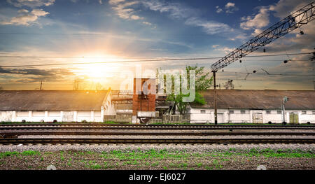 Rails and industrial station at the sunset - Stock Photo