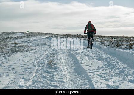 Mountain biker heading towards Win Hill in winter, Peak District, Derbyshire, England, UK. - Stock Photo