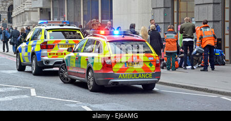 Medics and police with onlookers around a pedestrian on pavement requiring medical assistance with parked emergency - Stock Photo