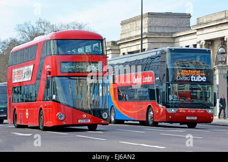 Regular London new Boris routemaster bus on local route 34 alongside inter city London to Oxford coach service run - Stock Photo