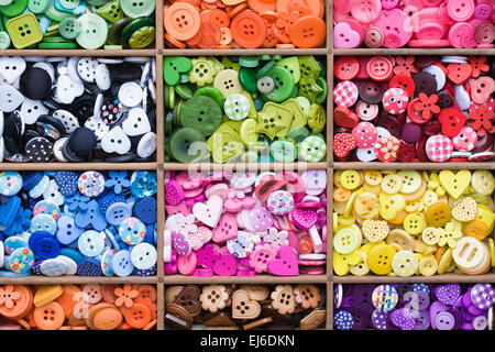 Colourful buttons in a wooden draw. - Stock Photo