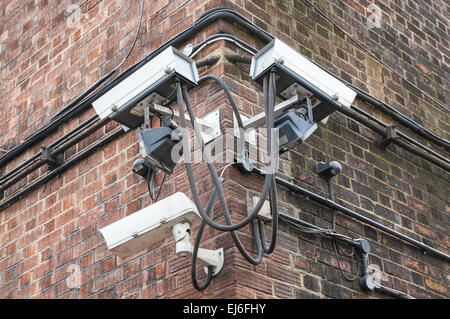 CCTV security cameras mounted on a brick building, London England United Kingdom UK - Stock Photo