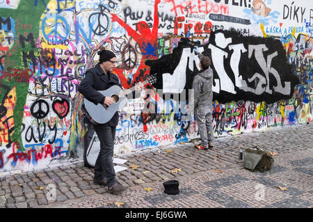 Busker and graffiti painter at the John Lennon Wall in Prague, Czech Republic - Stock Photo