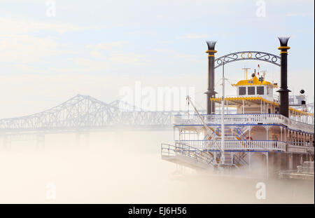 New Orleans, Louisiana. Creole Queen cruise ship on a foggy Mississippi river with Crescent City Connection bridge. - Stock Photo